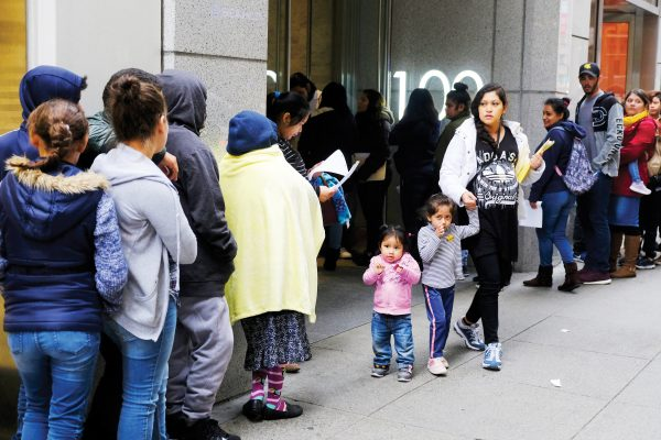 File - In this Jan. 31, 2019, file photo, hundreds of people overflow onto the sidewalk in a line snaking around the block outside a U.S. immigration office with numerous courtrooms in San Francisco. Federal judges are being asked to block a new Trump administration policy scheduled to take effect next week that would deny legal permanent residency to many immigrants over the use of public benefits. Almost a dozen lawsuits have been filed from New York to California to prevent the