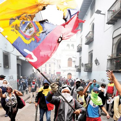 A protester waves a desecrated national flag during a march against President Lenin Moreno and his economic policies during a nationwide strike in Quito, Ecuador, Wednesday, Oct. 9, 2019. Ecuador's military has warned people who plan to participate in a national strike over fuel price hikes to avoid acts of violence. The military says it will enforce the law during the planned strike Wednesday, following days of unrest that led Moreno to move government operations from Quito to the port of Guayaquil. (AP Photo/Carlos Noriega)