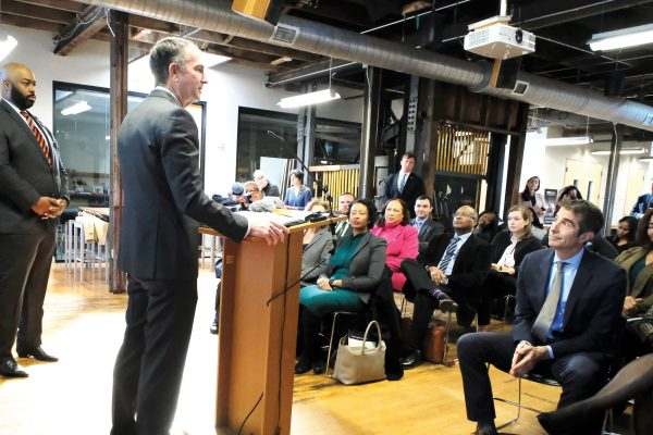 As Del. Lamont Bagby, D-Henrico, left, looks on, Gov. Ralph Northam, at podium,  adresses a gathering after recieving the report from The Commission to Examine Racial Enequity in Virginia Law in Richmond, VA Thursday, Dec. 5, 2019. (AP Photo/Richmond Times-Dispatch, Bob Brown).