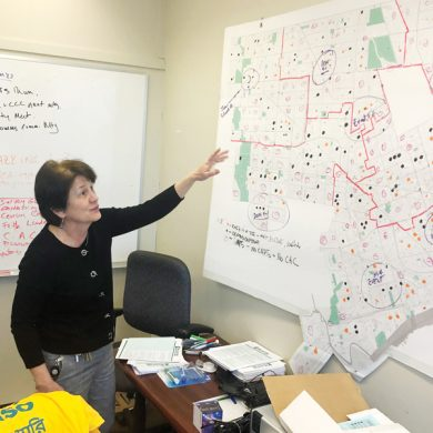 In this Nov. 22, 2019, photo, Detroit 2020 Census Campaign executive director Victoria Kovari looks over a Detroit map showing city neighborhoods that were under-counted in the 2010 census. In 2010, 220,000 Detroit residents were living in households that did not fill out questionnaires, costing the city $2,000 to $5,000 annually for every uncounted person, said Kovari. (AP Photo/Corey Williams)