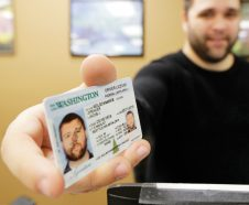 Ryan Norris, a license service representative at the Washington state Dept. of Licensing office in Lacey, Wash., poses for a photo Friday, June 22, 2018 while holding a sample copy of a Washington drivers license. Some Washington licenses and identification cards will soon be marked with the words