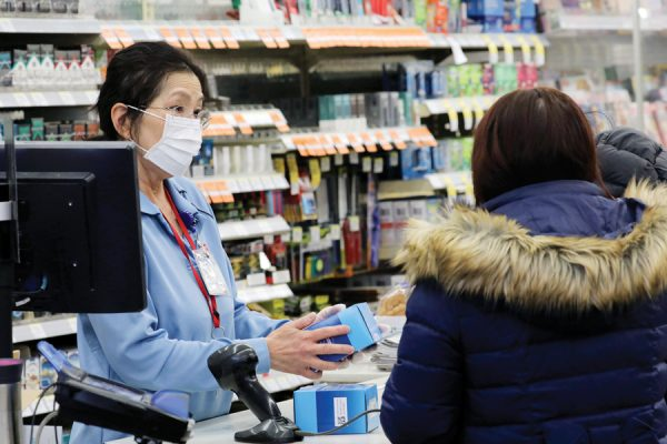 A sales clerk at a pharmacy rings up a purchase of face masks as fears of the coronavirus continues, Friday, Jan 24, 2020 in Chicago. A Chicago woman has become the second U.S. patient diagnosed with the dangerous new virus from China, health officials announced Friday. (Antonio Perez/Chicago Tribune via AP)