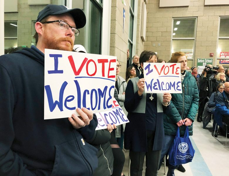 FILE - In this Dec. 9. 2019, file photo, residents in support of continued refugee resettlement hold signs at a meeting in Bismarck, N.D. A federal judge agreed Wednesday, Jan. 15, 2020, to block the Trump administration from enforcing an executive order allowing state and local government officials to reject refugees from resettling in their jurisdictions. U.S. District Judge Peter Messitte in Maryland issued a preliminary injunction requested by three national refugee resettlement agencies that sued to challenge the executive order. (AP Photo/James MacPherson, File)