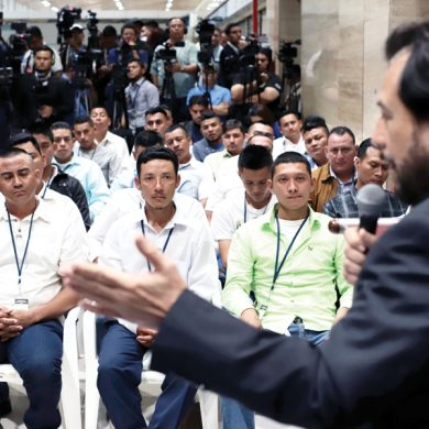 A group of Salvadorans granted temporary visas to work on a rose farm in Mississippi listen to Vice President Felix Ulloa during a send-off event at El Salvador International Airport in San Luis Talpa, El Salvador, Thursday, Dec. 19, 2019. The first group of 50 workers departed Thursday for the US, under a migrant worker program that is granting visas for 100 Salvadorans to spend several months working in the US agricultural sector. (AP Photo/Salvador Melendez)