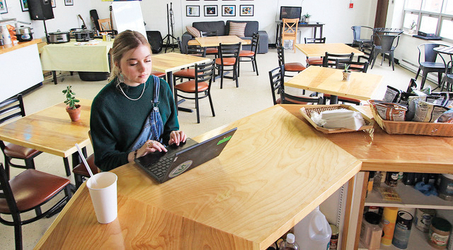 The Hub Cafe' employee Chloe Mansheim waits to answer the phone for curbside meal orders in Lewisburg, W.Va., Tuesday, March 17, 2020. The after school gathering place has temporarily closed its indoor seating area due to the coronavirus threat but are still offering free take-out meals for students. The location is able to offer 40-50 free meals a day. (Jenny Harnish/The Register-Herald via AP)