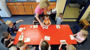 In this May 11, 2011 photo, teacher Kristie Niebeling hands out snacks to children during an Early Childhood Family Education program in Waconia, Minn. The district's elementary schools are so packed, they had to create space in one of the district warehouses for early childhood classes. (AP Photo/Craig Lassig)