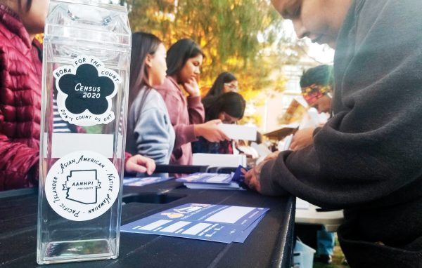 In this Jan. 3, 2020, photo, a woman fills out a pledge card for the U.S. Census in exchange for a reusable boba tea carton at a boba drink competition in Phoenix. The coronavirus has waylaid efforts to get as many people as possible to take part in the census. (AP Photo/Terry Tang)