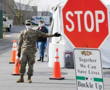A member of the Maryland National Guard directs a vehicle at a coronavirus drive-thru testing location at a Vehicle Emissions Inspection Program (VEIP) station in Curtis Bay, Md., Wednesday, April 1, 2020. Maryland opened three drive-thru testing sites for residents who are symptomatic or at high risk of complications from COVID-19. The tests are offered at three vehicle emissions testing sites in Anne Arundel, Charles and Harford counties. (AP Photo/Susan Walsh)