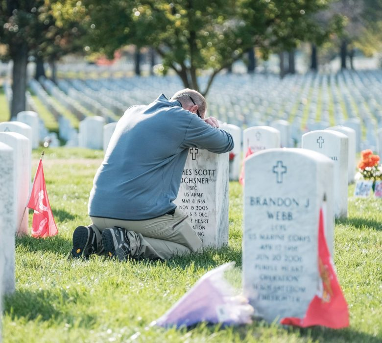 Army veteran Chris Plank pays respects at friends' grave on Veteran's Day at the Arlington National Cemetery, in Arlington, Virginia on Monday, Nov. 11, 2019. (AP Photo/Michael A. McCoy)