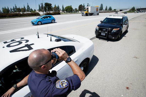 California Highway Patrol officer Matthew Musselmann uses a lidar gun for speed detection along Interstate 5 freeway, Thursday, April 23, 2020, in Anaheim, Calif. The CHP is issuing a lot more tickets to motorists where lanes are wide open during the coronavirus pandemic. From March 19, when the stay-at-home order began, through April 19, officers issued 87% more citations to drivers suspected of speeding in excess of 100 mph. That's compared to the same period last year. The jump in speeding tickets coincides with a 35% decline in traffic volume. (AP Photo/Chris Carlson)