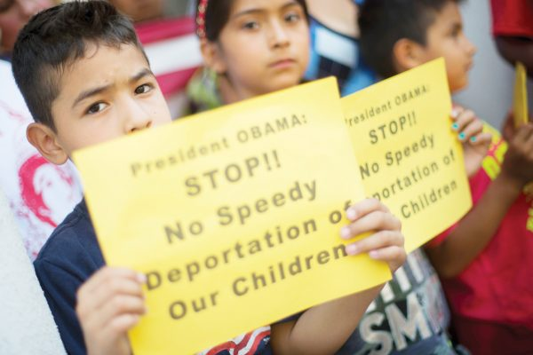 From left, Raul Amador Sanchez, 7, from Georgia, Alexandra Diaz, 9, and her brother Andy Diaz, 7, both from Baltimore, Md., hold up signs as they join their parent during a news conference of immigrant families and childrenís advocates responding to the President Barack Obamaís response to the crisis of unaccompanied children and families illegally entering the US, Monday, July 7, 2014, on the steps of St. John's Church in Washington. A top Obama administration official says no one, not even children trying to escape violent countries, can illegally enter the United States without eventually facing deportation proceedings. But Homeland Security Sec Jeh Johnson basically acknowledged Sunday that such proceedings might be long delayed, and he said that coping with floods of unaccompanied minors crossing the border is a legal and humanitarian dilemma for the US. (AP Photo/Pablo Martinez Monsivais)