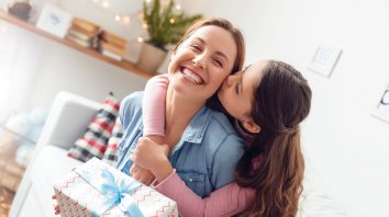 Young woman and girl at home celebrating mother's day sitting on sofa daughter hugging mother kissing cheek mom laughing joyful holding gift box