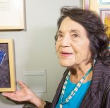 Dolores Huerta, co-founder of United Farms Workers shows her Presidential Medal of Freedom Award, as she tours her exhibition,