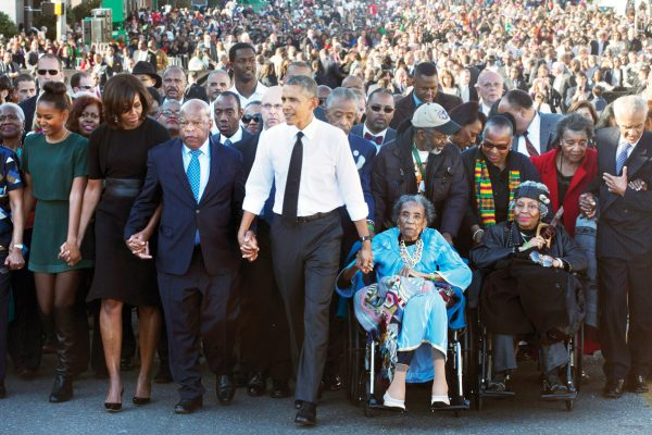 President Barack Obama, center, holds hands with Rep. John Lewis, D-Ga., left, and Amelia Boynton Robinson, right, who were both beaten during