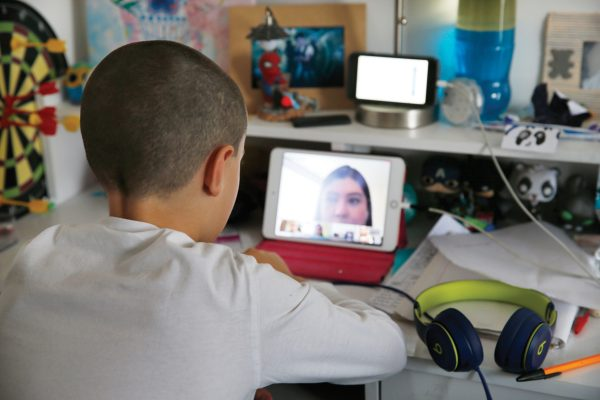Andres Rodriguez, 8, attends virtual classes from his room in an apartment in Mexico City, Thursday, April 23, 2020. Andres along with his sister Raquel, father Bernardo Rodriquez and mother Patricia Fernandez have self-quarantined for the last three weeks to protect themselves against the spread of the new coronavirus. (AP Photo/Marco Ugarte)