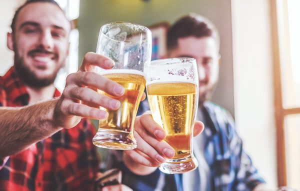 Two bearded hipsters clinking glasses of beer at bar