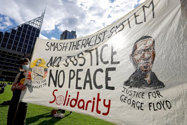 A man holds a banner showing George Floyd as thousands gather at a rally supporting the Black Lives Matter and Black Deaths in Custody movements in Sydney, Sunday, July 5, 2020. (AP Photo/Rick Rycroft)