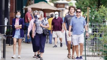 Pedestrians with and without face masks walk in downtown Omaha, Neb., Friday, July 31, 2020. Douglas County Health Director Dr. Adi Pour said she won't issue an order requiring people in the county and Omaha to wear masks to help slow the spread of the coronavirus, despite a unanimous vote by the county's health board to do so. The rejection of the health board's mandate came after Gov. Pete Ricketts and the state attorney general's office contacted local authorities to insist that such a requirement would violate state law. (AP Photo/Nati Harnik)