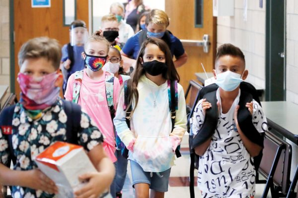 Wearing masks to prevent the spread of COVID19, elementary school students walk to classes to begin their school day in Godley, Texas, Wednesday, Aug. 5, 2020. Three rural school districts in Johnson County were among the first in Texas to head back to school for in person classes for students. (AP Photo/LM Otero)