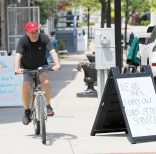 A cyclist rolls by signs outside of small business along Main Street in Bel Air, Md., Friday, May 15, 2020. Beginning Friday evening, small business and retailers will be allowed to reopen with some guidelines after Maryland Gov. Larry Hogan lifts a stay-at-home oder. (AP Photo/Julio Cortez)