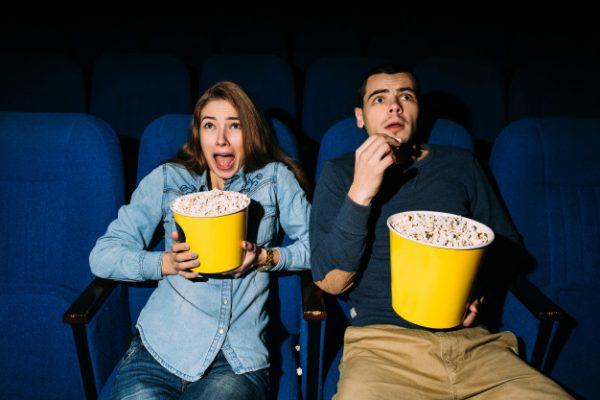 dia-cine-pareja-jovenes-palomitas-mirando-pelicula-terror-cine-su-fecha_8353-6559