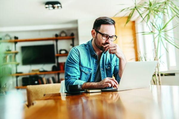 Pensive man looking at laptop while sitting at wooden table, portrait.